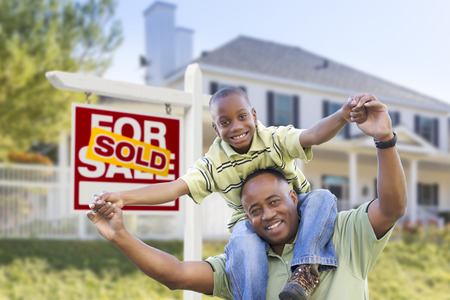 house sale: Happy African American Father and Son in Front of Home and Sold For Sale Real Estate Sign. Stock Photo