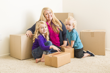 relocating: Happy Young Family in Empty Room With Moving Boxes.