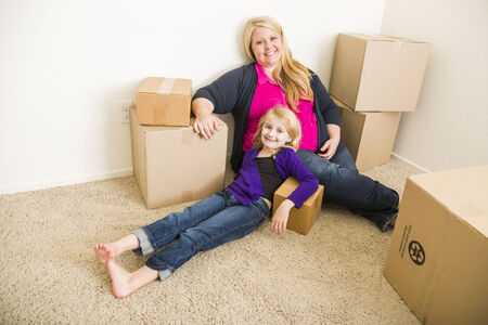 single parent: Happy Young Mother and Daughter In Empty Room With Moving Boxes.