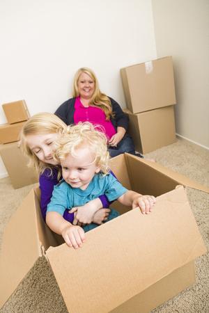 madre soltera: Familia juguetona joven en la habitación vacía jugando con cajas de mudanza. Foto de archivo