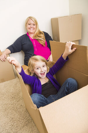 single parents: Playful Young Family In Empty Room Playing With Moving Boxes. Stock Photo