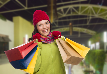 warmly: Pretty Warmly Dressed Mixed Race Woman In Outdoor Mall with Shopping Bags.
