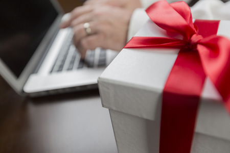 ecommerce: White Gift Box with Red Ribbon and Bow Near Man Typing on Laptop Computer.
