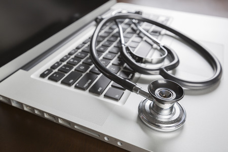 Medical Stethoscope Resting on Laptop Computer Keyboard. Banque d'images