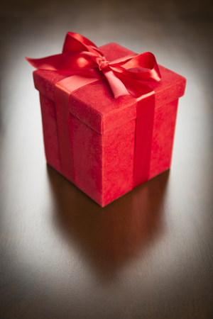 delivery room: Red Gift Box with Ribbon and Bow Resting on Wood Surface.