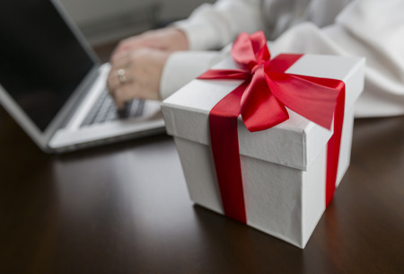 White Gift Box with Red Ribbon and Bow Near Man Typing on Laptop Computer. photo