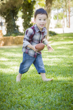 Cute Young Mixed Race Boy Playing Football Outside At The Park. photo