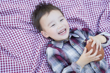 Cute Young Mixed Race Boy Playing With Football Outside On Picnic Blanket. photo