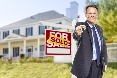 Real Estate Agent with House Keys in Front of Sold Sign and Home. Stock fotó