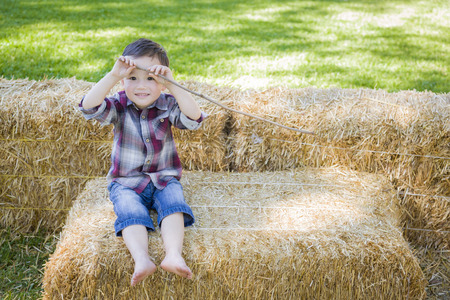 bale: Cute Young Mixed Race Boy Having Fun on Hay Bale Outside.