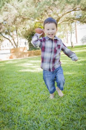 niño corriendo: Muchacho joven lindo raza mezclada que juega fútbol fuera en el parque.