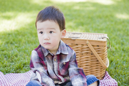 multi ethnic children: Cute Young Mixed Race Boy Sitting in Park Near Picnic Basket.