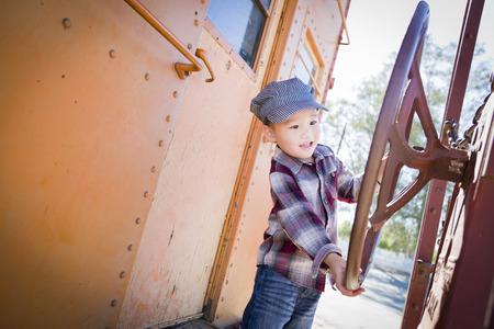 multi ethnic children: Cute Young Mixed Race Boy Having Fun Outside on Railroad Car.