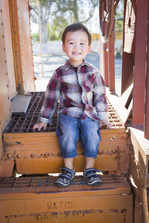 caboose: Cute Young Mixed Race Boy Having Fun Outside Sitting on Railroad Car Steps.