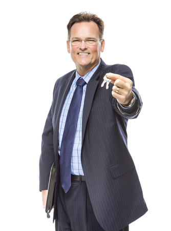 Handsome Real Estate Agent Holding Out Keys to New Home Isolated on a White Background. Stock fotó