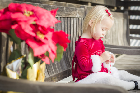 Adorable Little Girl Sitting On A Bench with Her Candy Cane Outside. photo