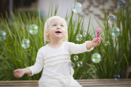 Adorable Little Girl Sitting On Bench Having Fun With Bubbles Outside. photo
