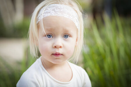 Adorable Little Girl with Blue Eyes Portrait Outside. photo