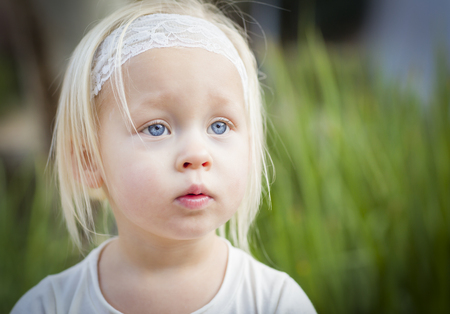 Adorable Little Girl with Blue Eyes Portrait Outside. Stock Photo