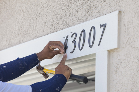 finishing touches: House Painter Contractor Nails Address Numbers onto House Facade.