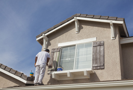 finishing touches: Busy House Painter Painting the Trim And Shutters of A Home.