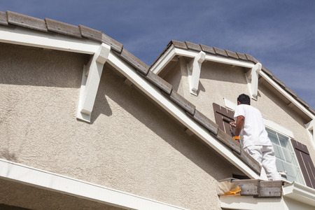 residential structures: Busy House Painter Painting the Trim And Shutters of A Home.