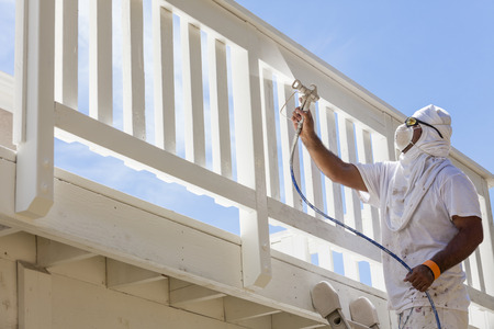 home remodel: House Painter Wearing Facial Protection Spray Painting A Deck of A Home.