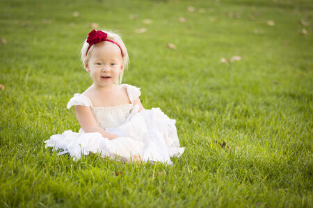 Beautiful Adorable Little Girl Wearing White Dress Sitting In A Grass Field. photo