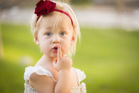 hair band: Beautiful Adorable Little Girl With Her Finger on Her Mouth Wearing White Dress In A Grass Field.
