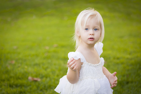 Beautiful Adorable Little Girl Wearing White Dress In A Grass Field. photo