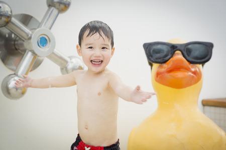 pato de hule: Mixed Race Boy Having Fun en el parque acuático con gran pato de goma en el fondo. Foto de archivo