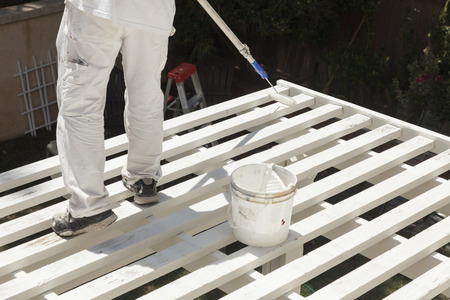 Painter Rolling White Paint Onto The Top of A Home Patio Cover. photo
