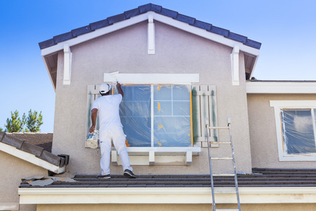 home improvements: Busy House Painter Painting the Trim And Shutters of A Home.
