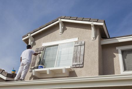 working at home: Ocupado Pintor Pintura de casa la moldura y persianas de una vivienda.