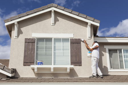 house facades: Busy House Painter Painting the Trim And Shutters of A Home.