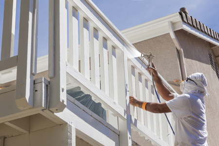 site: House Painter Wearing Facial Protection Spray Painting A Deck of A Home.