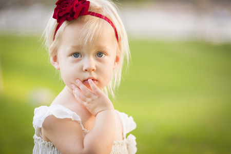 Beautiful Adorable Little Girl With Her Hand On Her Face Wearing White Dress In A Grass Field. photo