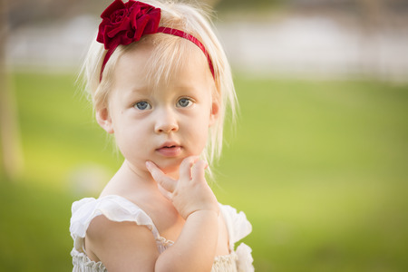 hair band: Beautiful Adorable Little Girl With Her Hand On Her Face Wearing White Dress In A Grass Field.