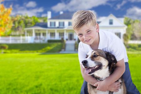 Gelukkige Jonge jongen en zijn hond in de voortuin van hun huis.