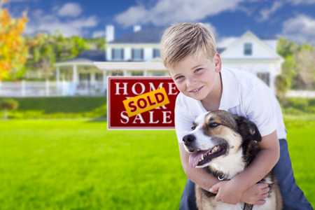 Happy Young Boy and His Dog in Front of Sold For Sale Real Estate Sign and House. photo
