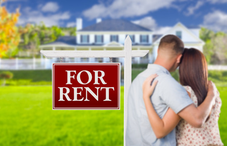 for rent sign: For Rent Real Estate Sign and Affectionate Military Couple Looking at Nice New House.