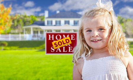 Cute Smiling Girl in Front Yard with Sold For Sale Real Estate Sign and House. photo
