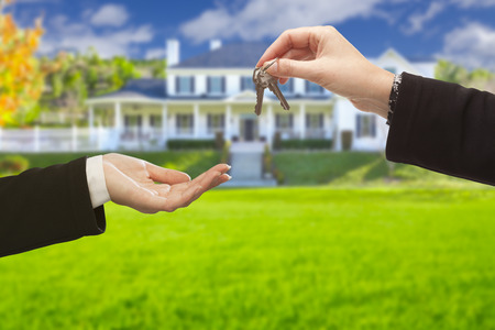 Real Estate Agent Handing Over the House Keys in Front of a Beautiful New Home.
