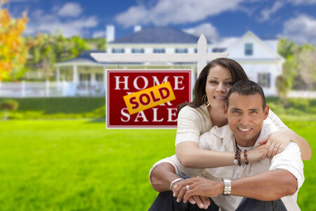 new age: Young Happy Hispanic Young Couple in Front of Their New Home and Sold For Sale Real Estate Sign.
