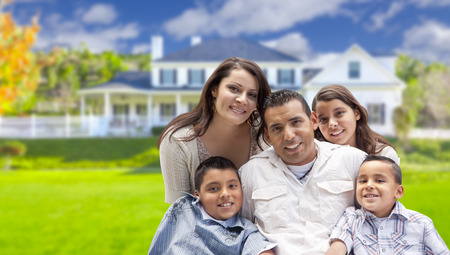 home front: Happy Young Hispanic Family in Front of Their New Home. Stock Photo