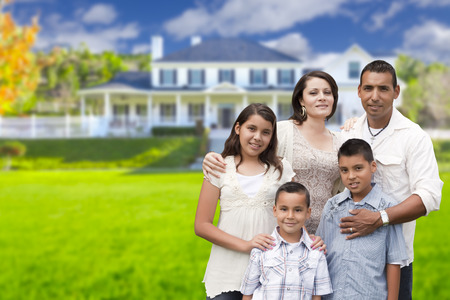 standing: Happy Young Hispanic Family in Front of Their New Home. Stock Photo