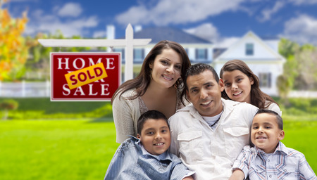 spanish home: Happy Hispanic Family in Front of Their New House and Sold Home For Sale Real Estate Sign.