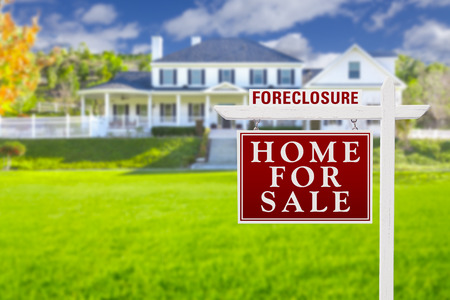 dispossession: Foreclosure Home For Sale Real Estate Sign in Front of Beautiful Majestic House. Stock Photo
