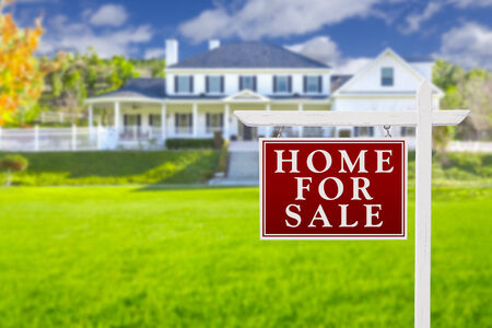 Home For Sale Real Estate Sign in Front of Beautiful New House. Stock Photo