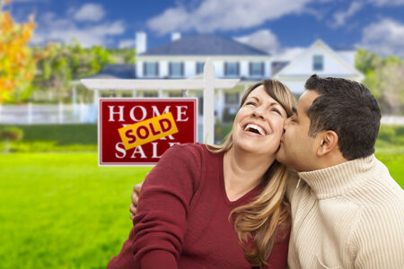 Happy Mixed Race Couple in Front of Sold Real Estate Sign. photo